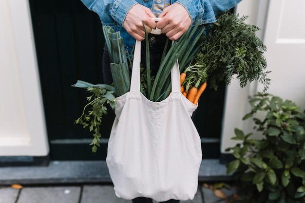 Abschluss einer person, die weiße einkaufslebensmittelgeschäfttasche hält, füllte mit gemüse