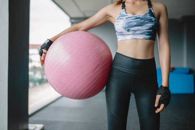 Abschluss herauf asiatisches frauenmodell hält yogaball an der turnhalle, die für übung, übungsmädchen sich vorbereitet
