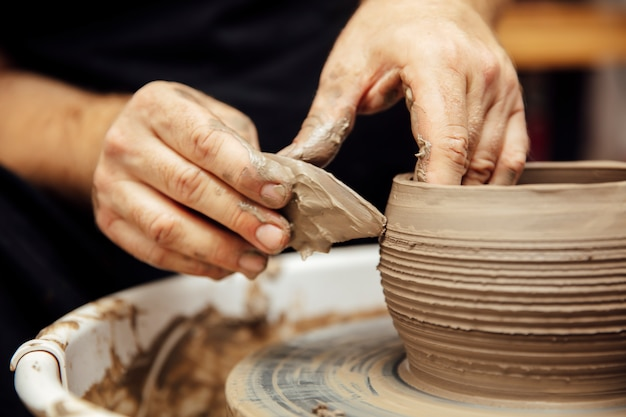 Abschluss herauf detailansicht bei einem künstler macht lehmtonwaren auf einem spinnrad