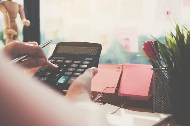 Abschluss herauf die geschäftsfrau, die taschenrechner und laptop für verwendet, tun mathefinanzierung auf hölzernem schreibtisch im büro- und geschäftsarbeitshintergrund, in der steuer, in der buchhaltung, in den statistiken und im analytischen forschungskonzept