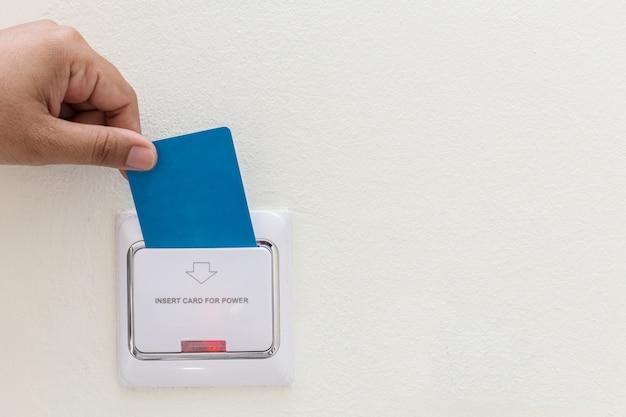 Abschluss herauf die hand, die blauen hotelschlüsselkarteneinsatz hält, um schalter anzutreiben