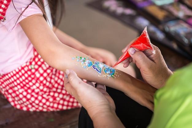 Abschluss herauf die hand von den leuten, die kunstfarbe auf kinderarm machen