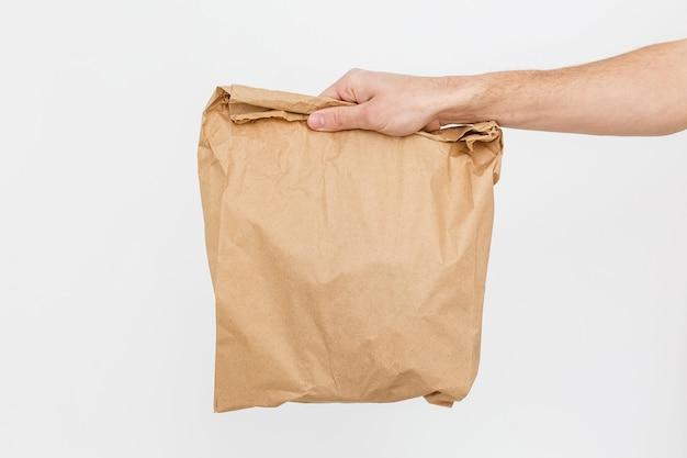 Abschluss herauf frau hält in der hand braune klare leere leere kraftpapiertüte