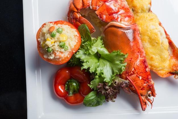 Abschluss herauf hummer backen mit dem käse, der in der hälfte geschnitten wurde, die mit feuerreis in der tomate instand gehalten wurde.