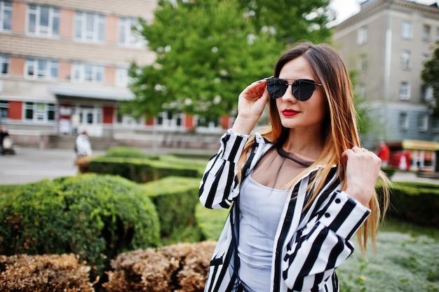 Abschluss herauf porträt des blickes der modernen frau mit der gestreiften schwarzweiss-anzugsjacke und sonnenbrille, die gegen büsche an der straße aufwerfen. konzept des modemädchens.