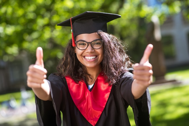 Abschluss. hübsches junges mädchen in akademischer mütze, das sich über den abschluss freut