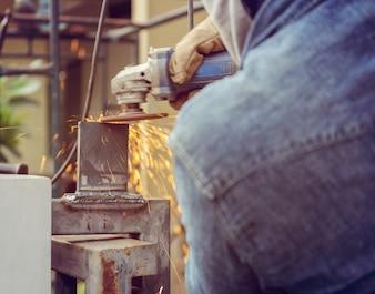 Abschluss oben der Flamme funkt mit elektrischem Schleifer, sägende Metallfunken der Arbeitskraft während des Arbeitens