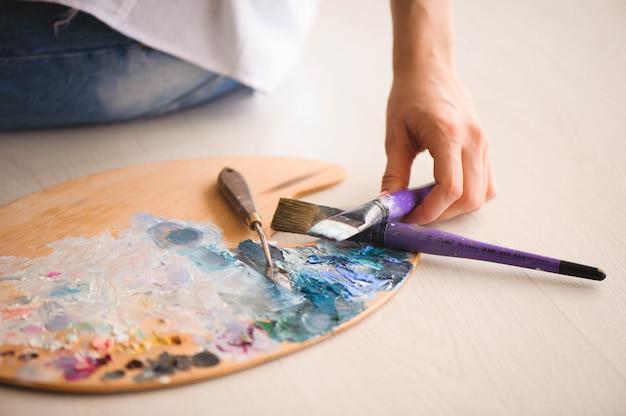 Abschluss oben der frauenhandmischungsfarben mit pinsel in der palette im kunstunterricht