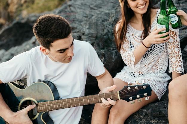 Abschluss oben der freunde am strand mit gitarre