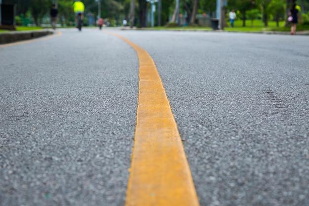 Abschluss oben der gelben linie auf dem allgemeinen park mit leuten trainieren und radfahren für gutes gesundheit backgro