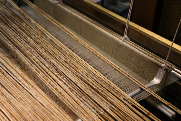 Abschluss oben der goldseide, die auf webstuhl spinnt