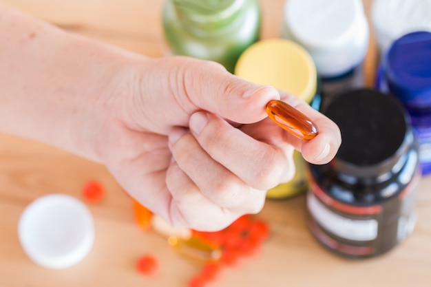 Abschluss oben der hand hält eine vitaminergänzung auf medizinflaschenhintergrund