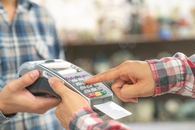 Abschluss oben der hand unter verwendung der kreditkarte, die maschine wäscht, um zu zahlen