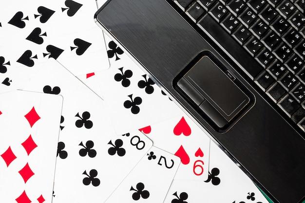 Abschluss oben der laptoptastatur auf spielkartenhintergrund.