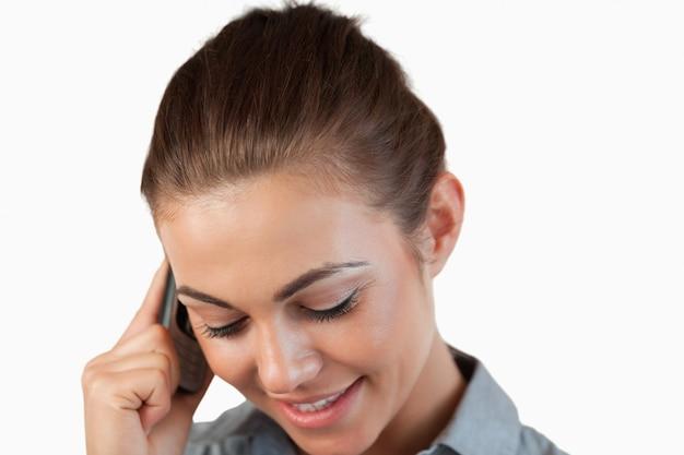 Abschluss oben der schüchternen lächelnden geschäftsfrau am telefon