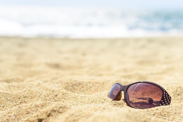 Abschluss oben der sonnenbrille auf dem strand