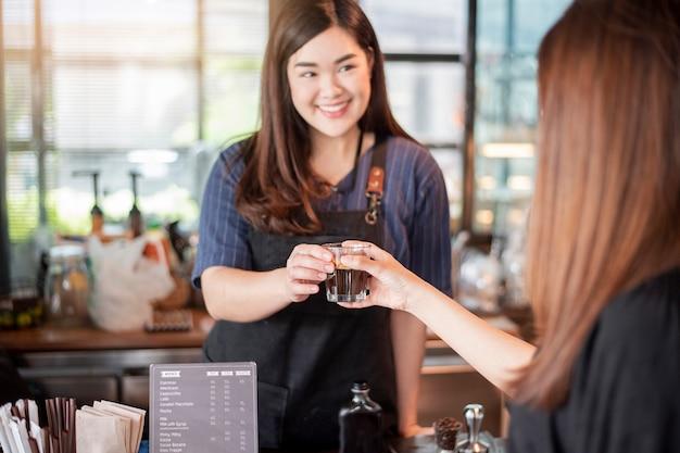 Abschluss oben der weiblichen hand nimmt heißen kaffee von barista