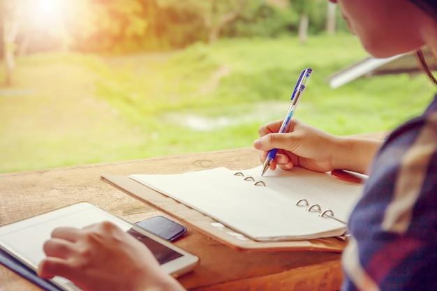 Abschluss oben der zufälligen frauenhand hält mobilen smartphone und schreibt anmerkungen in notizbuch