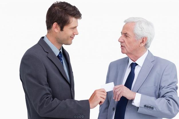 Abschluss oben des geschäftsmannes, der dem handelspartner visitenkarte gibt