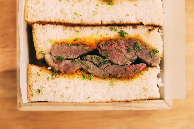 Abschluss oben des japanischen halbwändigen wagyu-sandwiches diente in der holzkiste.