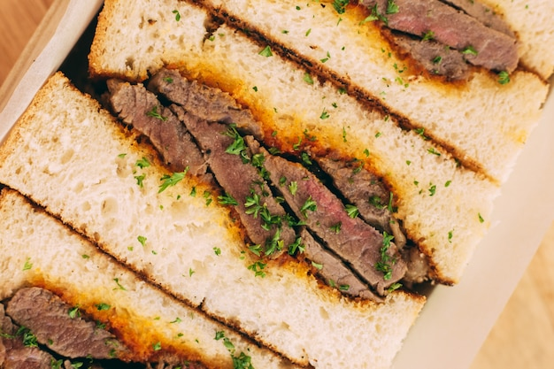 Abschluss oben des japanischen halbwändigen wagyu-sandwiches diente in der holzkiste