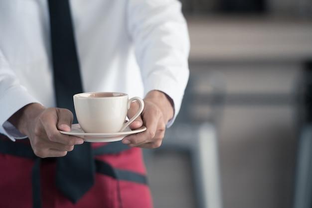 Abschluss oben des kellners, der einen tasse kaffee im café dient.