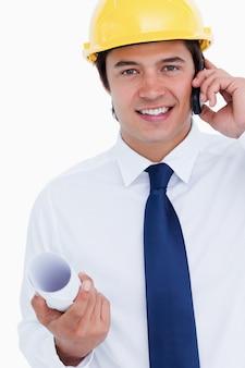 Abschluss oben des lächelnden männlichen architekten auf seinem mobiltelefon
