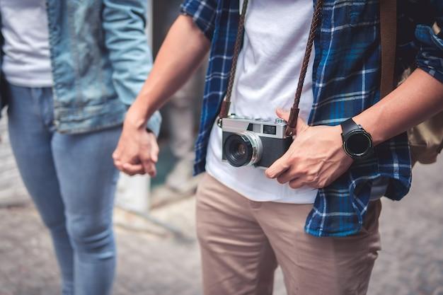 Abschluss oben des liebevollen paarhändchenhaltens auf einer straßenstadt und einer hängenden kamera