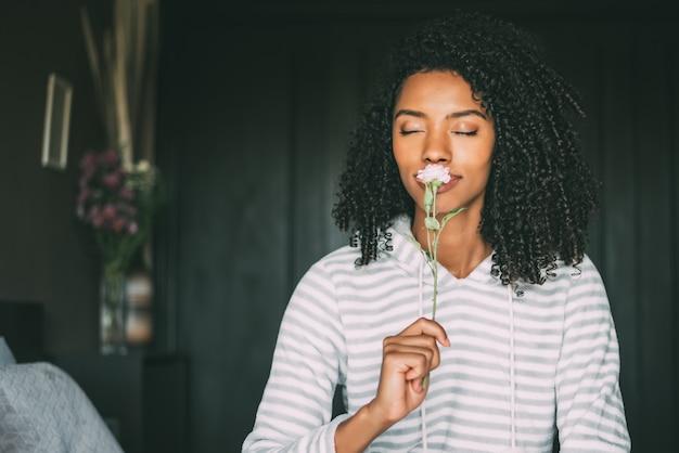Abschluss oben einer hübschen schwarzen frau mit dem gelockten haar, das eine rosenblume riecht, sitzen auf bett