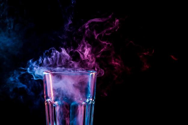 Abschluss oben eines neuen glases mit weichem mehrfarbigem rosafarbenem rauche vom vape auf einem schwarzen getrennten hintergrund