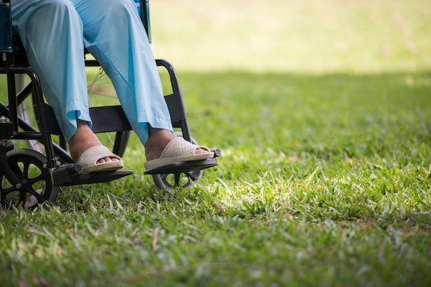 Abschluss oben einsame ältere frau, die auf rollstuhl am garten im krankenhaus sitzt