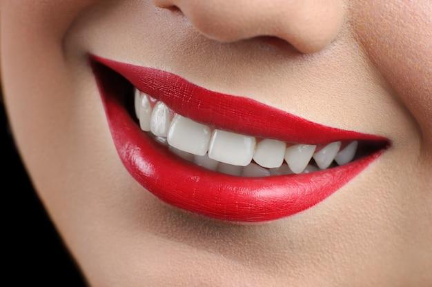 Abschluss oben geernteter schuss eines perfekten lächelns einer roten lippigen frau