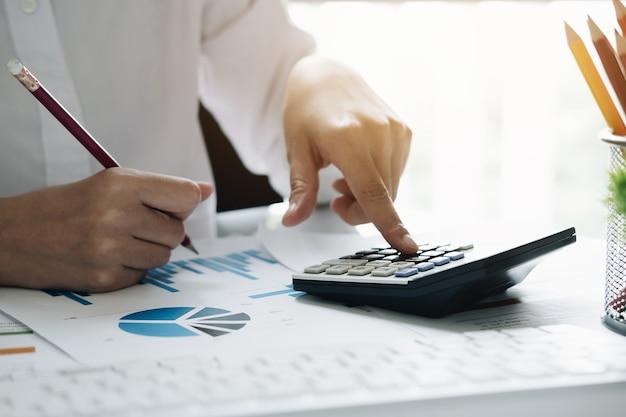 Abschluss oben geschäftsfrau, die taschenrechner für tut mathe verwendet, finanzieren auf hölzernem schreibtisch im büro