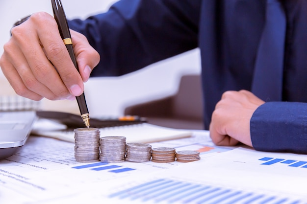 Abschluss oben, hand, die geldmünzenstapel in das sparen des geldes und in wachsendes geschäftskonzept einsetzt.