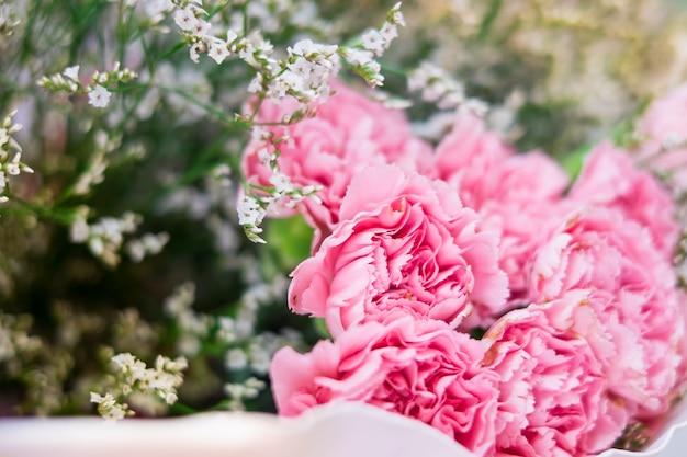 Abschluss oben rosa blumen sind im blumenstrauß, der mit weißen blumen und backg des selektiven fokus vereinbart wird