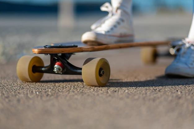 Abschluss oben von damenbein in den weißen turnschuhen, die nach extremer lustiger fahrt ihr hölzernes longboard skateboard, modernes städtisches hippie-mädchen stillstehen, haben spaß, guten sonnigen sommertag für das skateboard fahren und haben spaß