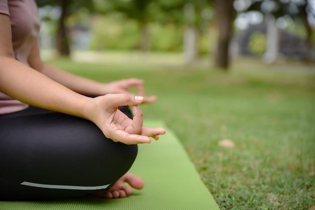 Abschluss oben von frauenhänden tut yoga draußen im park.