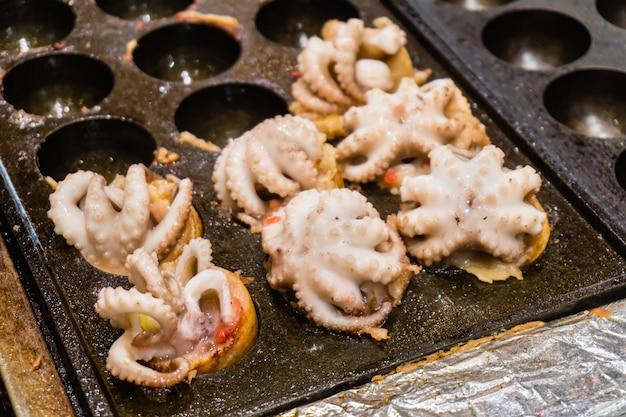 Abschluss oben von takoyaki mit dem kalmar, making takoyaki durch großen tintenfisch wählen sie fokus aus. japanisches essen