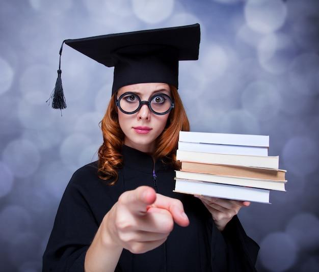 Abschluss studentin in einem akademischen kleid mit büchern