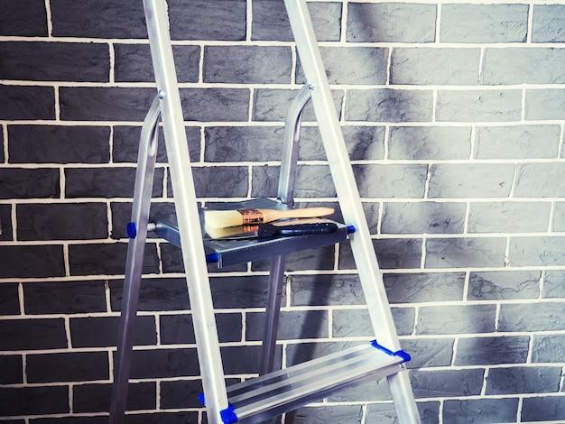 Abschlussarbeiten in einem neu gebauten haus. trittleiter und dekorationswerkzeuge in der nähe der wand. reparaturwerkzeuge