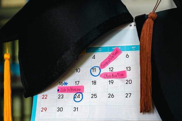 Abschlussfeier abschlusskappe auf weißem sauberem kalender