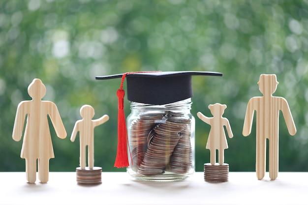 Abschlusshut auf glasflasche mit modellfamilie und stapel münzgeld auf natürlichem grünem hintergrund, geld sparen für bildung und familienfinanzierungskonzept
