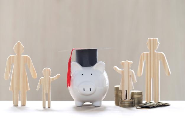 Abschlusshut auf glasflasche mit modellfamilie und stapel münzgeld auf weißem hintergrund, geld sparen für bildung und familienfinanzierungskonzept