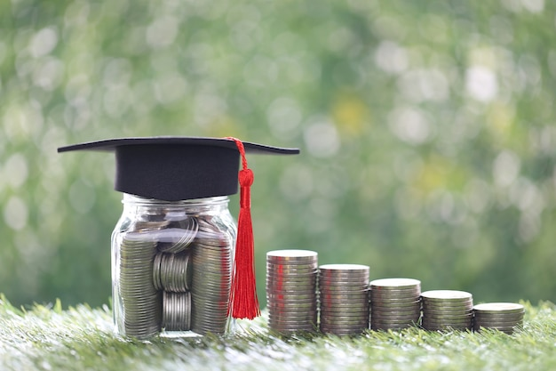 Abschlusshut auf glasflasche und stapel münzgeld auf natürlichem grünem hintergrund, geld sparen für bildung und familienfinanzierungskonzept