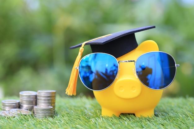 Abschlusshut auf goldenem sparschwein mit sonnenbrille und stapel von geldmünzen auf natürlichem grün