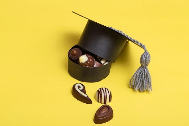 Abschlusskappe in form einer box. eine schachtel pralinen, schwarz, milchschokolade. high school abschluss. farbiger hintergrund