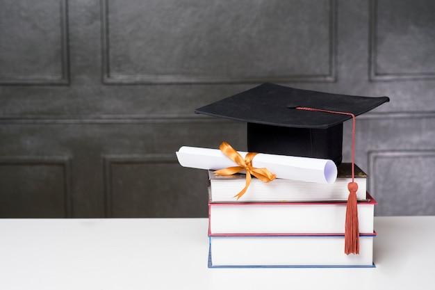Abschlusskappe mit büchern auf weißem schreibtisch, bildungshintergrund