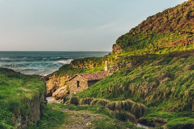 Abseits der ausgetretenen pfade. alte verlassene wassermühle am strand. grüner berg.