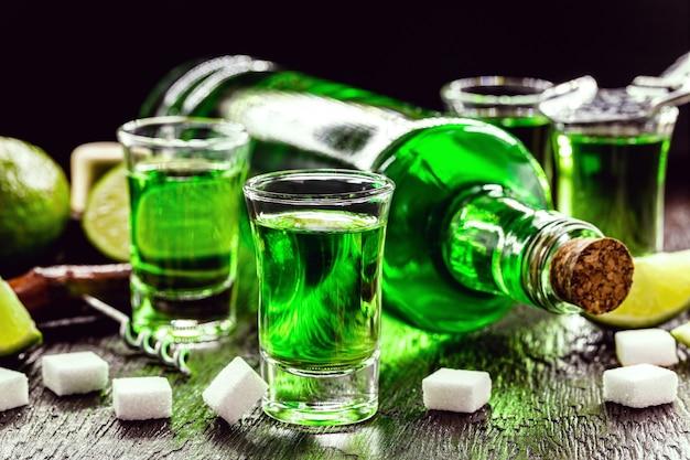 Absinthdosen mit zuckerwürfeln. absinthflasche, grünes destilliertes getränk