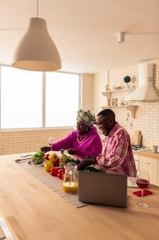 Absolut gesund. nettes afroamerikanisches paar, das gemüse schneidet, während salat zubereitet